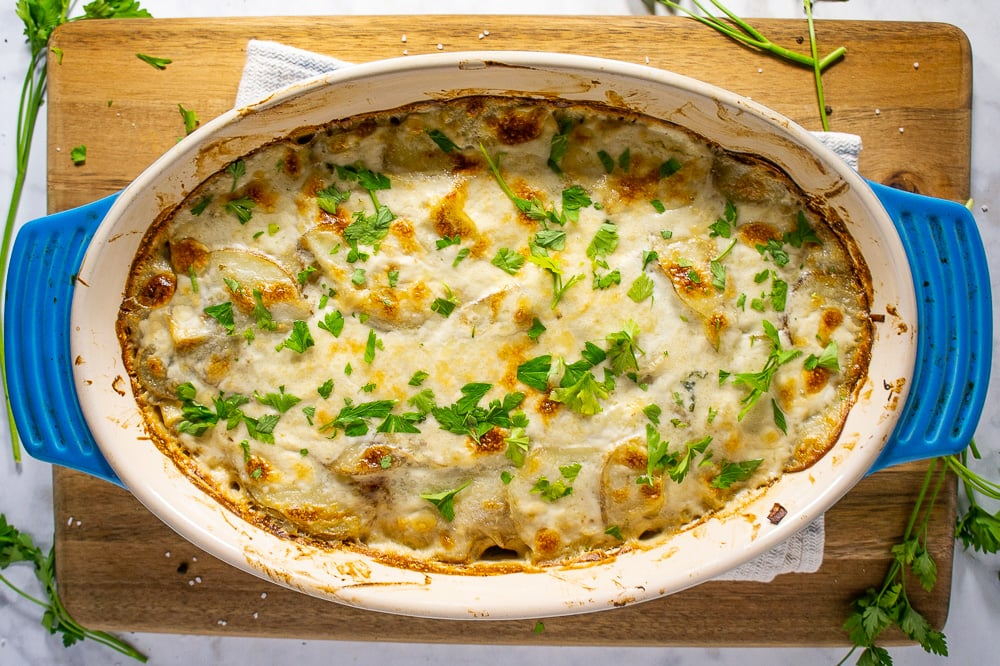 a blue casserole dish with golden brown scalloped potatoes topped with parsley on a cutting board on a white granite counter