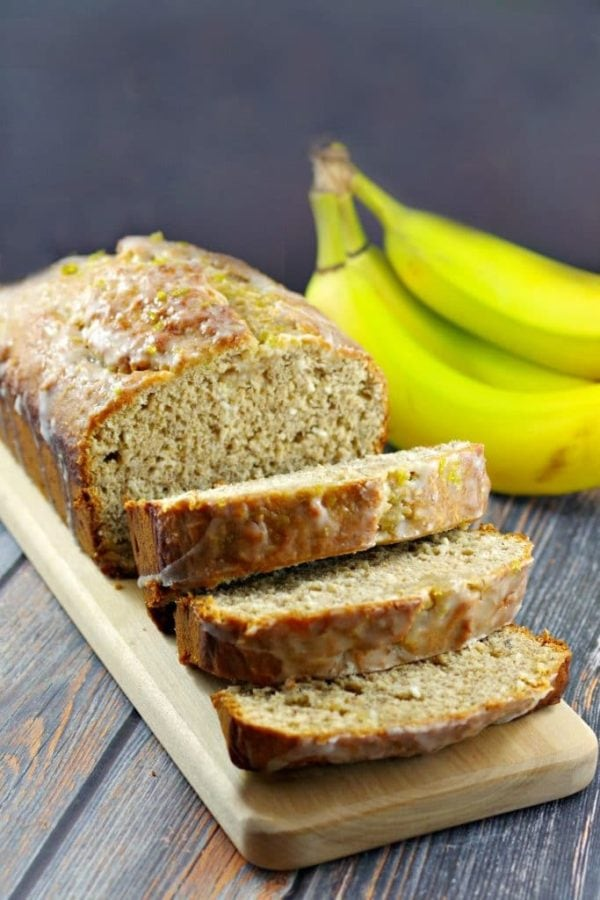 a sliced loaf of tropical banana bread on a wood platter on a wood table