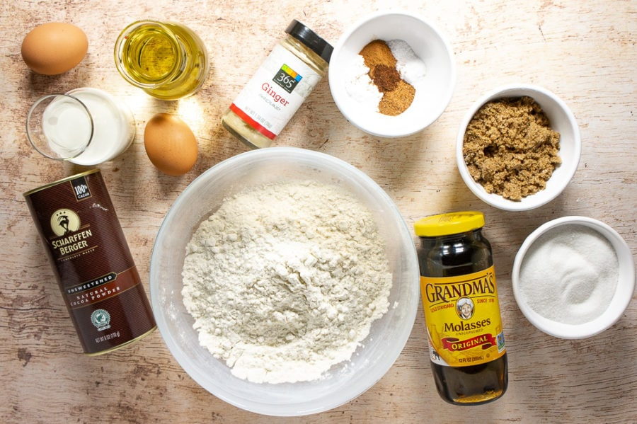 a bowl of flour on a wooden table surrounded by bowls of ingredients like sugars, spices, eggs, oil, milk, and molasses