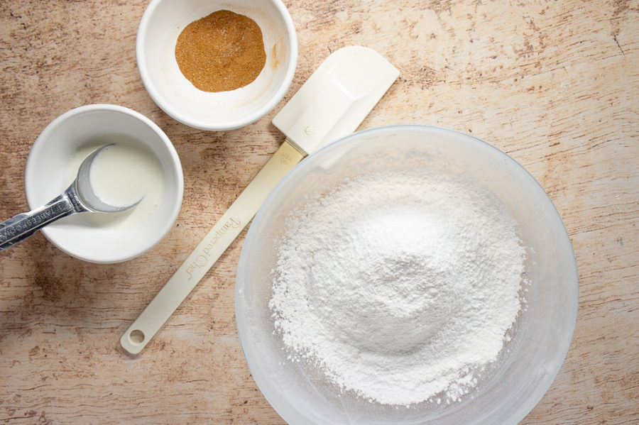 A bowl of powdered sugar, a small bowl of spices, and a small bowl of heavy cream with a tablespoon in it.