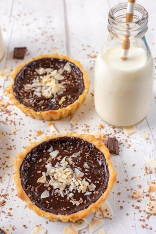 a small chocolate pie with coconut shavings on a white table by a glass of milk with a straw