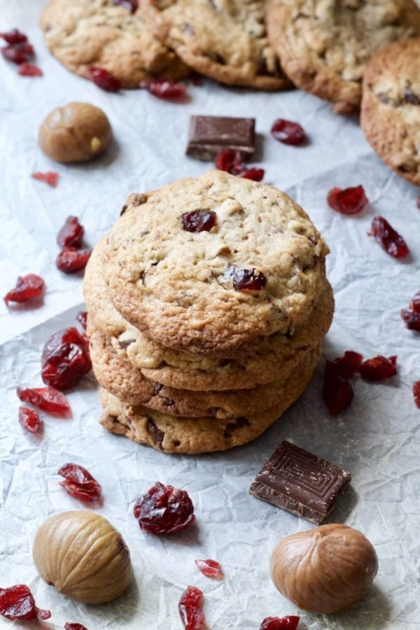 A stach of cranberry chocolate chip cookies surrounded by scattered cranberries, chocolate, and chestnuts
