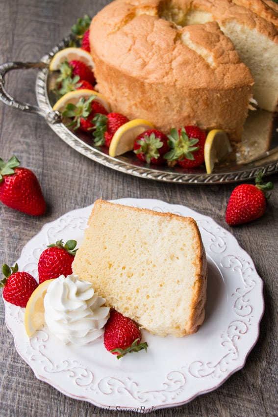 a slice of classic chiffon cake on a metal round platterwhite plate with strawberries in front of the rest of the cake on
