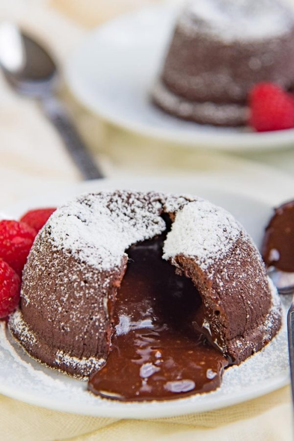 A molten chocolate cake cut open and oozing chocolate, dusted with powdered sugar on a white plate