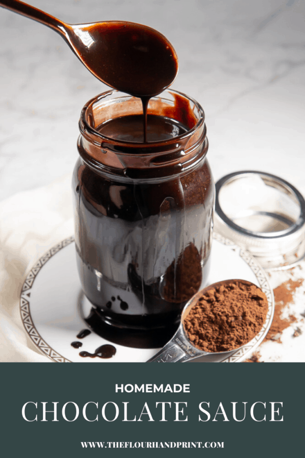 a white plate on a granite surface with a spoon of cocoa powder spilled around it. A jar of chocolate sauce on the plate with a spoon being lifted out of it.