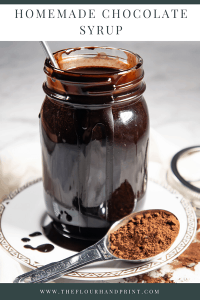 A jar of chocolate syrup with a spoon in it, on a white plate with drizzled chocolate and a spoon of cocoa powder on a white granite surface