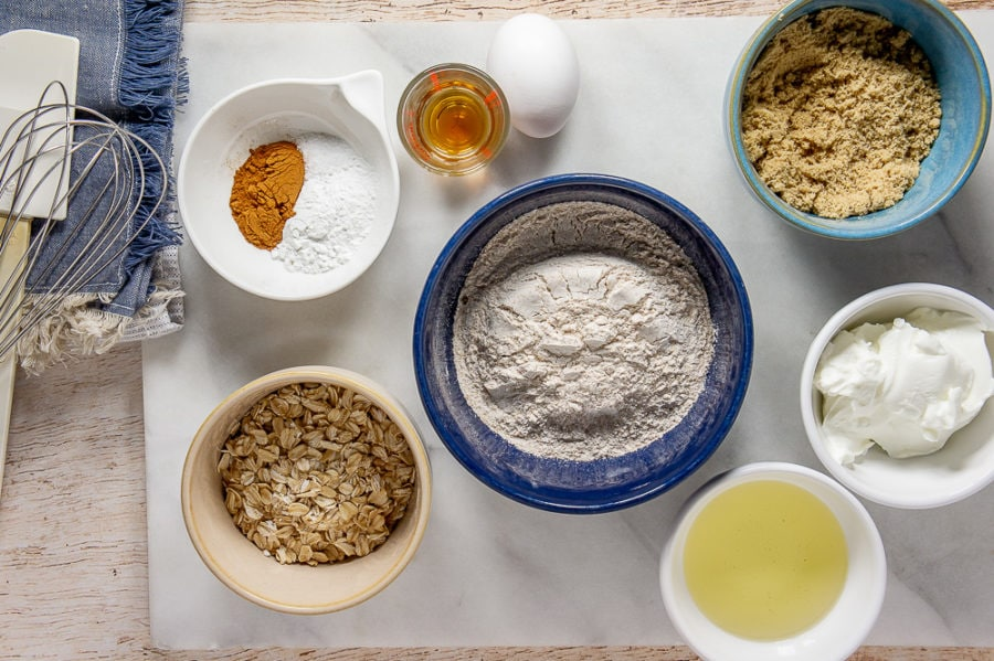 A white granite cutting board with a blue bowl of wheat flour, a blue bowl of brown sugar, a white bowl of yogurt, a white bowl of spices, a glass of vanilla, a brown bowl of oats, and a white bowl of oil sitting atop a wooden table with a blue fringed napkin next to it.