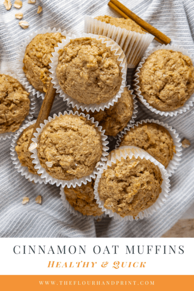A pile of oatmeal cinnamon muffins on a blue and white towel with scattered oats and cinnamon sticks