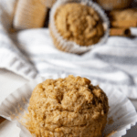 A singular oatmeal muffin with the white wrapper peeled away sitting on a wooden table in front of a pile of the remaining muffins on a blue and white striped towel in the background.