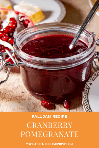 An open jar of cranberry jam on a wooden table surrounded by fresh cranberies