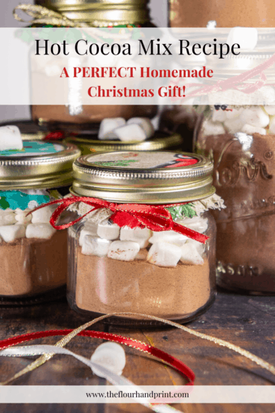 small mason jars of hot cocoa mix with marshmallows on top tied with bows and holiday fabric