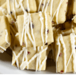 a white bowl of raspberry shortbread cookies drizzled with chocolate