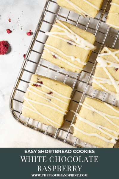 a metal cooling rack with white chocolate raspberry cookies and dried raspberries around it