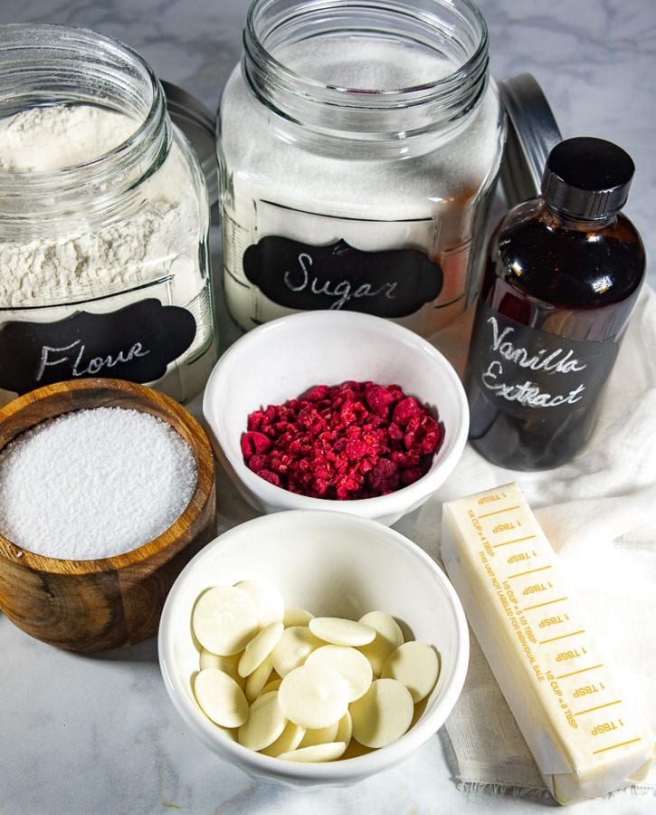 A white granite table with a glass jar of flour, a glass jar of sugar, a bottle of vanilla extract, a bowl of freeze dried raspberries, butter, white chocolate, and salt