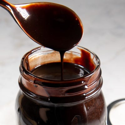 a spoon coated in chocolate syrup dripping into a jar of chocolate on a white granite surface