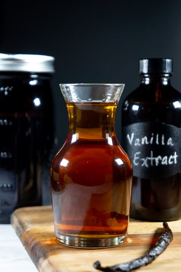 a decanter of vanilla extract on a wooden cutting board, a vanilla bean beside it, and a dark bottle of extract behind it.