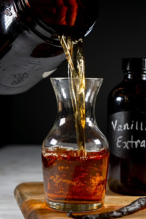 homemade vanilla extract being poured from a large amber mason jar into a decanter on a wooden cutting board beside a whole vanilla bean