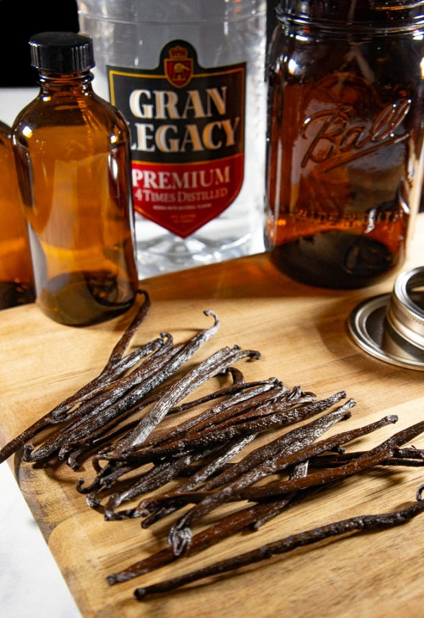 a pile of vanilla beans on a wooden cutting board with brown glass bottles behind it and a bottle of vodka