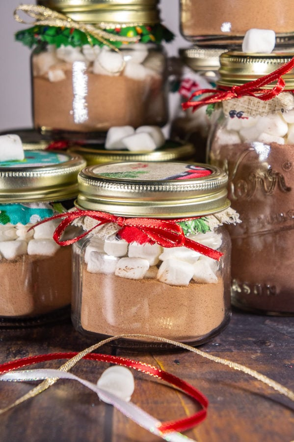 small mason jars full of hot cocoa mix and marshmallows sealed with christmas cloth and ribbons.
