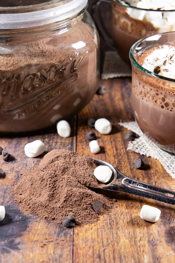 A large glass jar of hot cocoa mix with a spoonful scattered across the wooden table in front of it sitting beside two glasses of hot cocoa with whipped cream