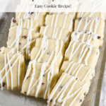 A grey rectangular platter with rows of shortbread cookies with white chocolate and freeze dried raspberries