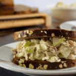 a chicken salad sandwich with dark crust on a white plate on a wooden table with sliced loaf of bread behind it