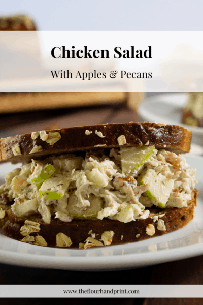 a chicken salad sandwich with pecans and apples on a white plate on a wood table