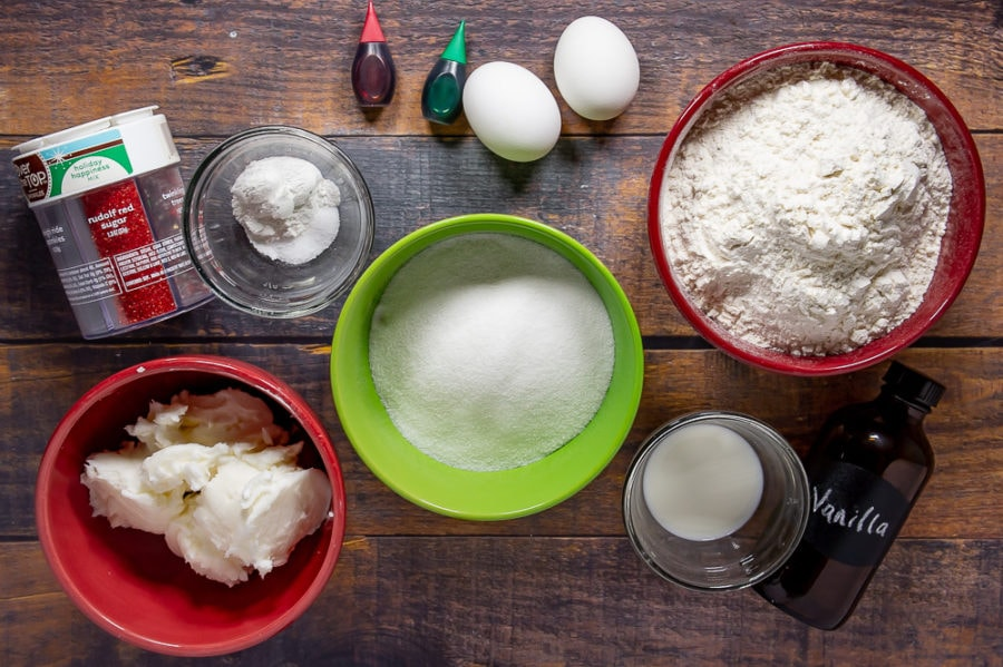 A red bowl of shortening, a green bowl of sugar, a red bowl of flour, a small glass bowl of milk, two eggs, sprinkles, and small bowl of baking powder on a wooden table