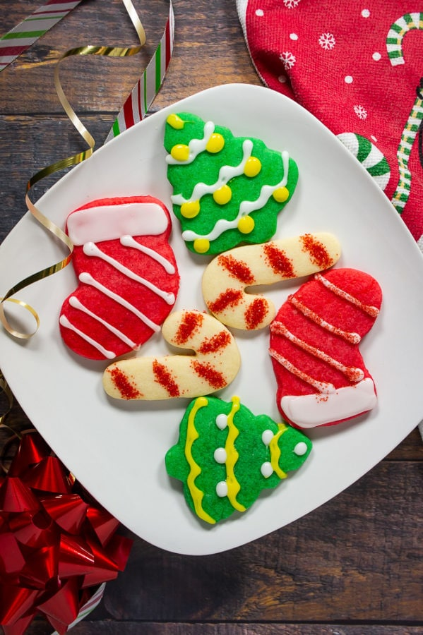 a white plate with two candy cane cookies, two green christmas tree cookies, and two red stocking cookies with white frosting on a wooden table beside a red christmas towel
