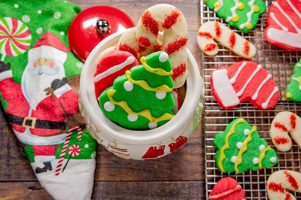 a santa towel beside a muffin cookie jar with sugar cookies and a cooling rack with cookies on a wooden table