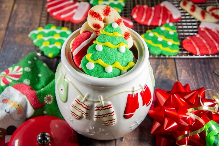a white christmas cookie jar brimming with colored sugar cookies on a wooden table in front of a metal cooling rack with more cookies