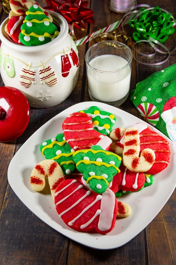 a white plate of red, green, and white sugar cookies shaped as trees, stockings, and candy canes on a wooden table in front of christmas decorations and a glass of milk