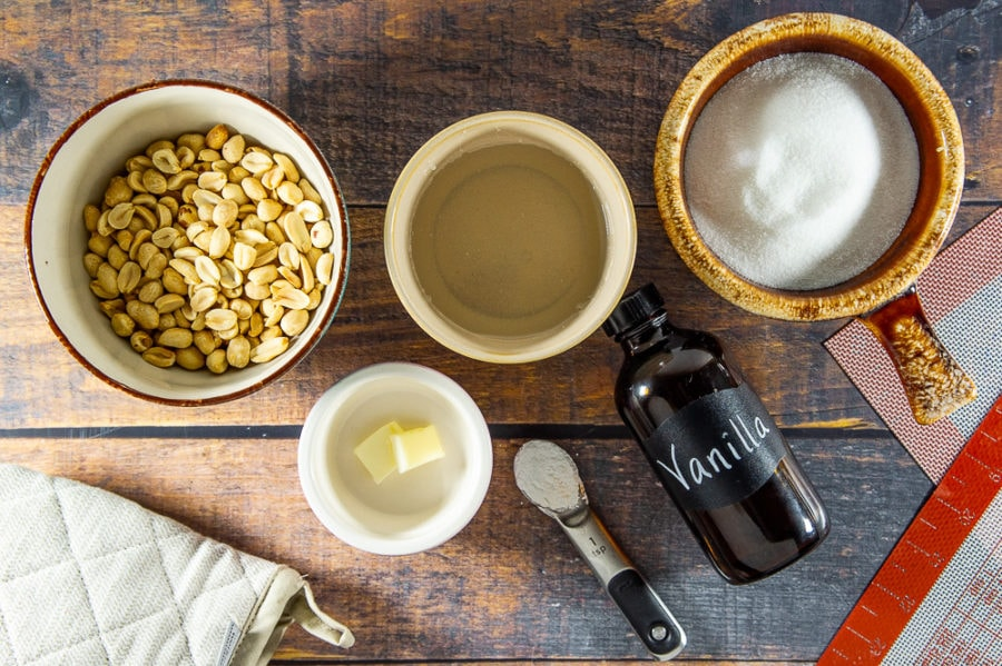 Ingredients for peanut brittle: a bowl of peanuts, a bowl of sugar, a bowl of karo syrup, a teaspoon of butter, and baking soda, and a bottle of vanilla on a wooden table