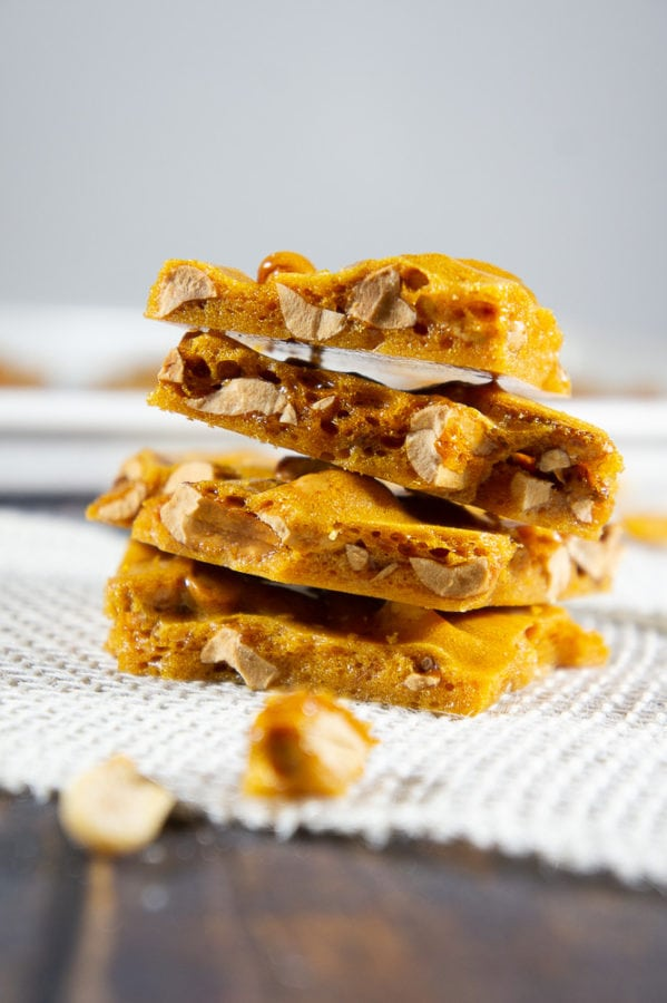 Stacked peanut brittle on a white burlap strip with scattered brittle shards around it