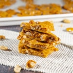 Four pieces of peanut brittle stacked on a burlap sheet on a wooden table with scattered peanuts and brittle around it
