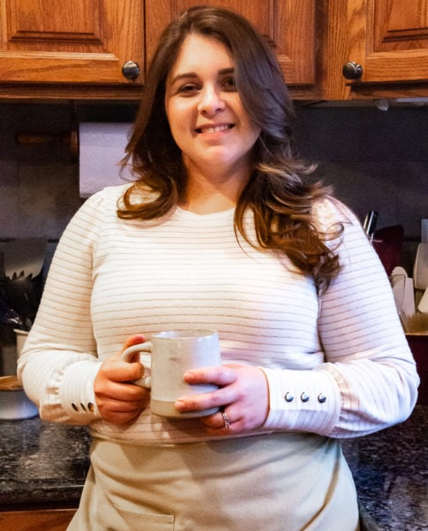 mikayla author of the flour handprint standing in a kitchen with a cup of coffee