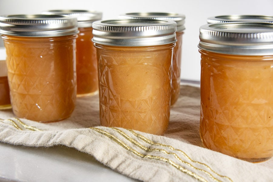 several jars of pear butter after being processed in a water bath on a tan towel