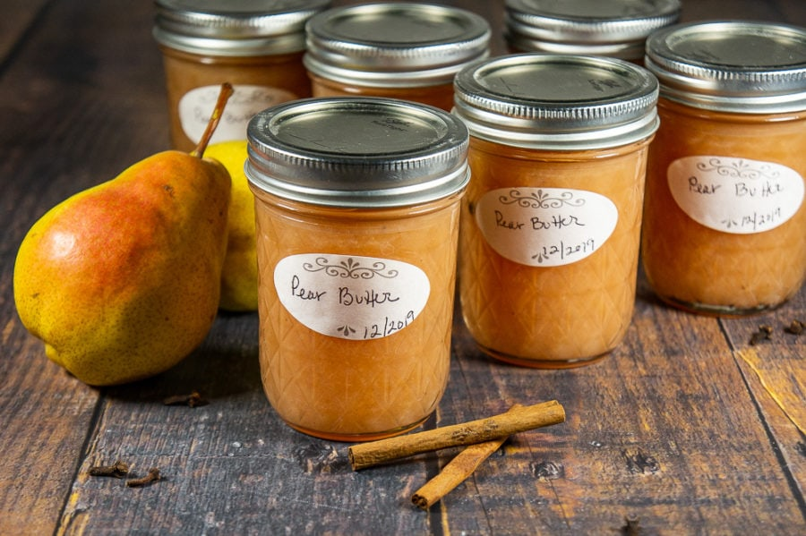 Six jars of pear butter on a wooden table with a whole pear and a few cinnamon sticks