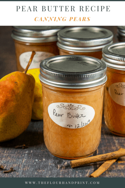 Several jars of pear butter on a wooden table with fresh pears and cinnamon sticks
