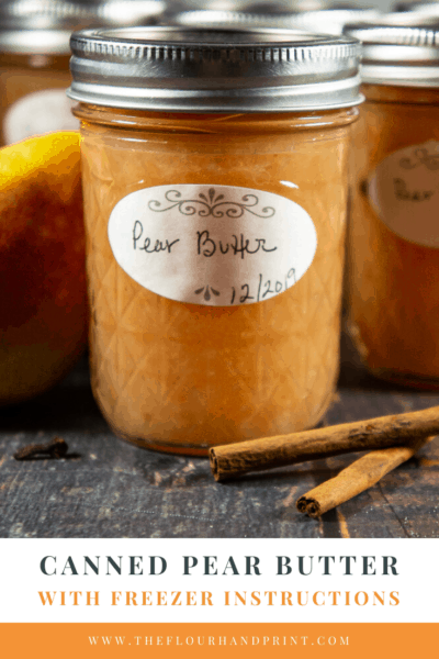 An 8 ounce jar of a pear butter recipe with two cinnamon sticks sitting beside it on a wooden table.