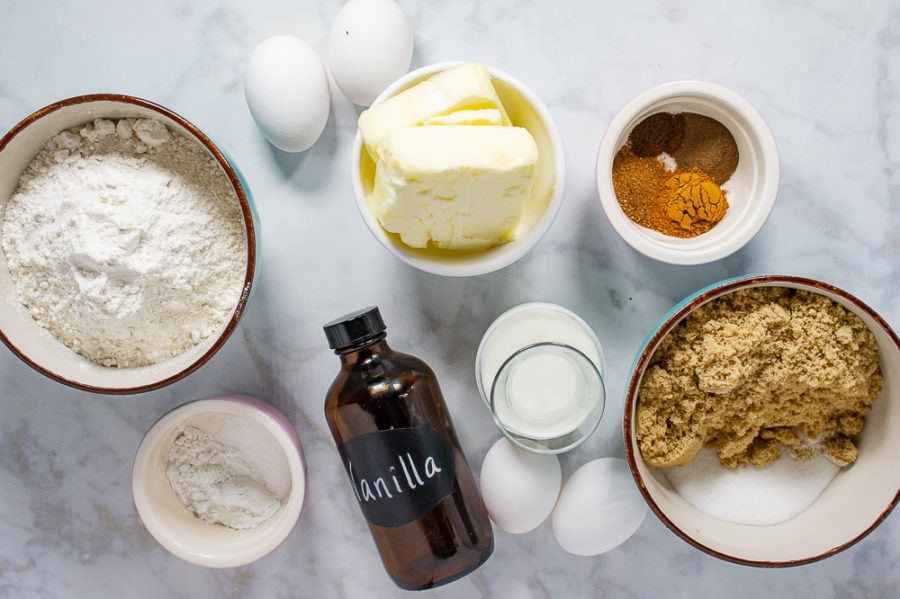a large bowl of flour and of sugars, four eggs, a bowl of butter, a bowl of spices, a bottle of vanilla, and a carafe of milk on a white granite surface