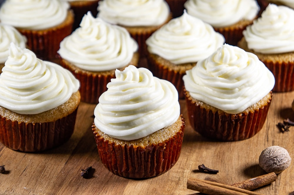 a wooden board of cupcakes with cream cheese frosting