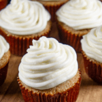 spice cake cupcakes with cream cheese frosting on a wooden board