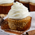 a spice cupcake with cream cheese frosting unwrapped on a grey towel beside a cinnamon stick in front of more cupcakes