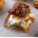 a bacon jam crostini with a bite taken out of it on a parchment paper with other crostinis around it.