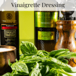 two bottles of oil, a bottle of balsamic vinaigretet, a pepper mill, salt, and fresh basil