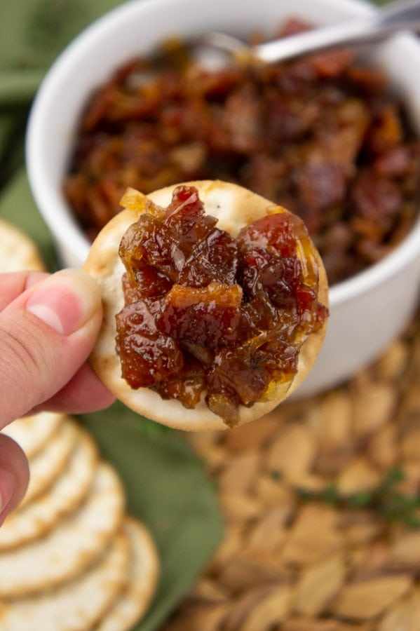 cracker with bacon jam held over a white bowl full of bacon jam