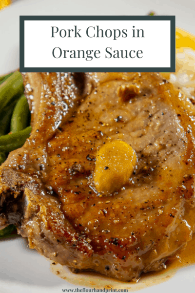 A single orange ginger pork chop with a slice of ginger on top of it