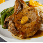 A white plate with green beans and rice and a orange pork chop