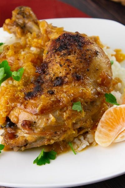 a chicken thigh braised with oranges over rice with parsley on a white plate